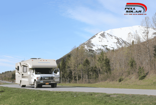 A tan RV is traveling down an open road with green grass and small forest trees beside the road. It is a sunny day, and a big mountain with snow on top of it is in the background.