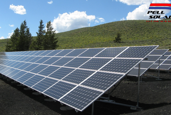 Large solar panels in a grassy field with hills.