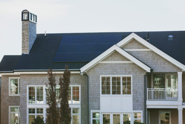 Grey and white modern home with solar panels on the roof.